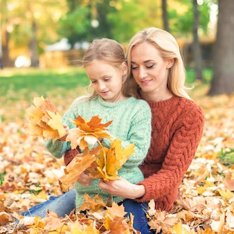 Woman and girl holding autumn yellow leaves