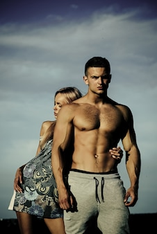 Woman or girl hug bodybuilder man with muscular torso on blue sky couple in love summer vacation rec...