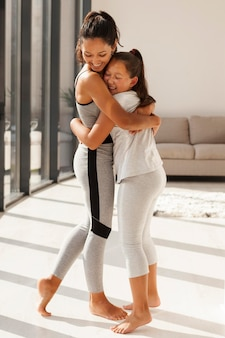 Woman and girl hugging full shot