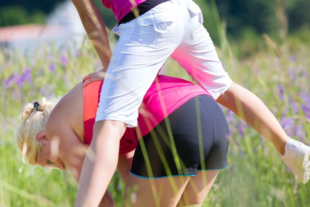 Woman and girl leapfrog in field