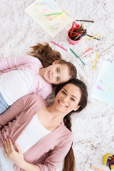 Woman and girl lie on white carpet with pencils.