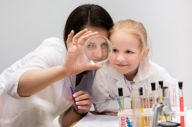 Woman and girl looking through magnifier
