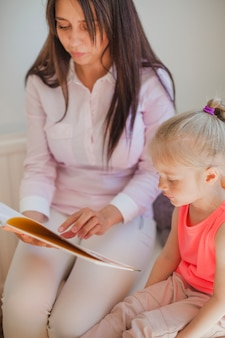 Woman and girl reading book together