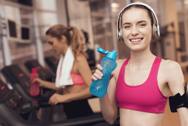 Woman and girl in sportswear running on treadmill at the gym