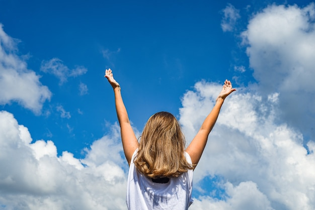 A woman, a girl stands backwards in a wheat field with her hands raised to the sky.