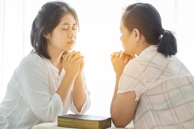 女性の女の子は家にいて神を祈り、崇拝します。祈りの少女は、コロナウイルスの危機のために家から礼拝し、祈ります。ホーム教会、オンライン教会、祈る手、自宅での礼拝