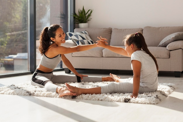 Woman and girl stretching together indoors