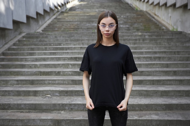 Woman or girl wearing black blank cotton t-shirt with space for your logo, mock up or design in casual urban style