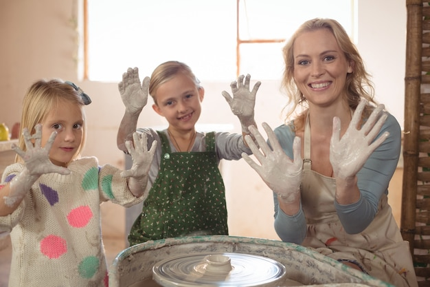 Woman and girls showing hands in pottery shop