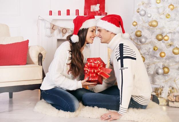 Женщина делает подарок мужчине на рождество