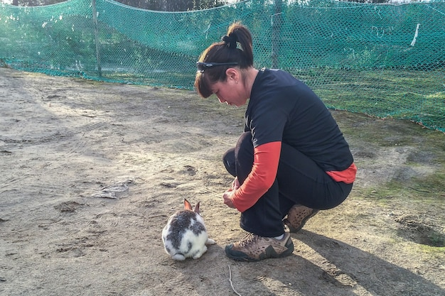 Woman gives food to rabbit. nature love and vegan concept