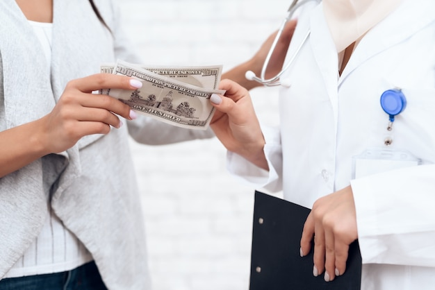 A woman gives money to a female doctor.