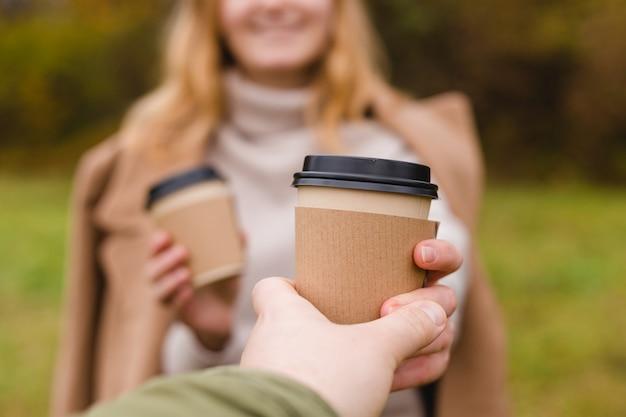 女性は紙のコーヒーカップを与える男性はカップを取る