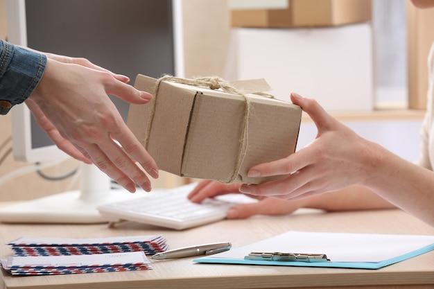 女性が郵便局で小包を与える