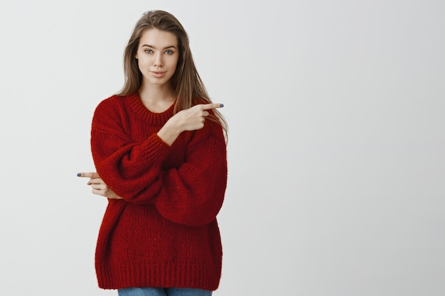 Woman gives us opportunity to chose way in life. confident feminine european girl in stylish red loose sweater, pointing in different directions, excepting every possibility