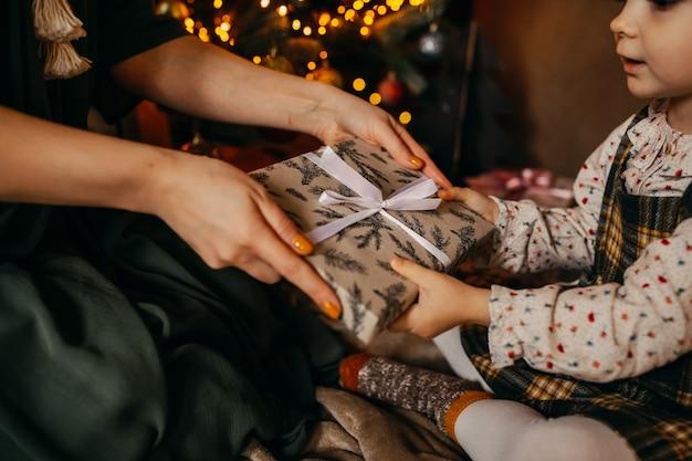 クリスマスツリーの横にある小さな女の子に贈り物をする女性
