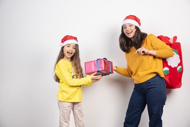 サンタクロースの赤い帽子をかぶった少女にプレゼントを贈る女性。