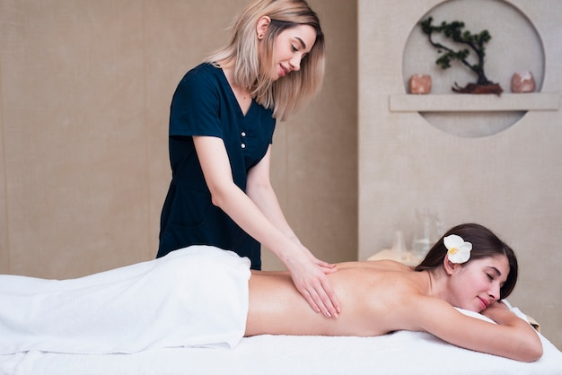 Woman giving back massage at spa