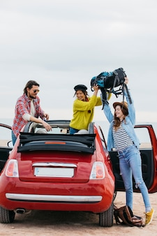 Woman giving backpack to lady near man leaning out from car