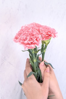 Woman giving carnations bouquet on marble white background, top view, copy space, close up.