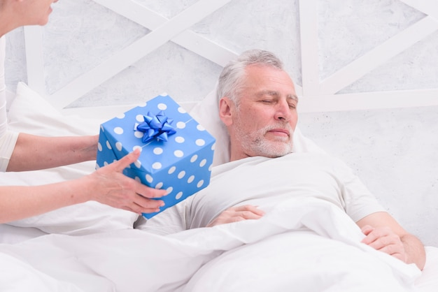 Woman giving gift to her husband sleeping on bed