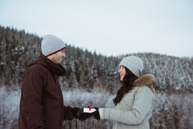 Woman giving gift to man on snow covered mountain