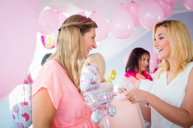 Woman giving gift to pregnant friend on baby shower