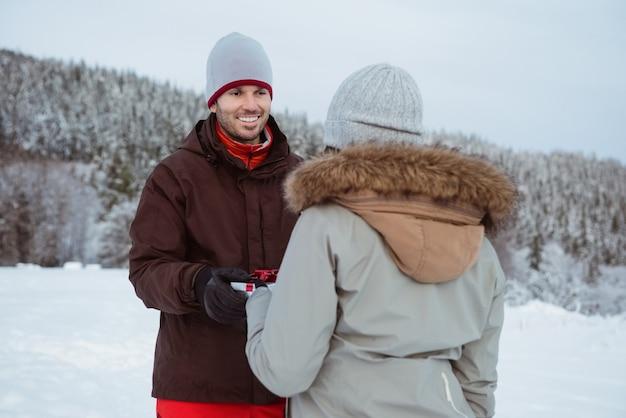 雪に覆われた山で男性に贈り物をする女性
