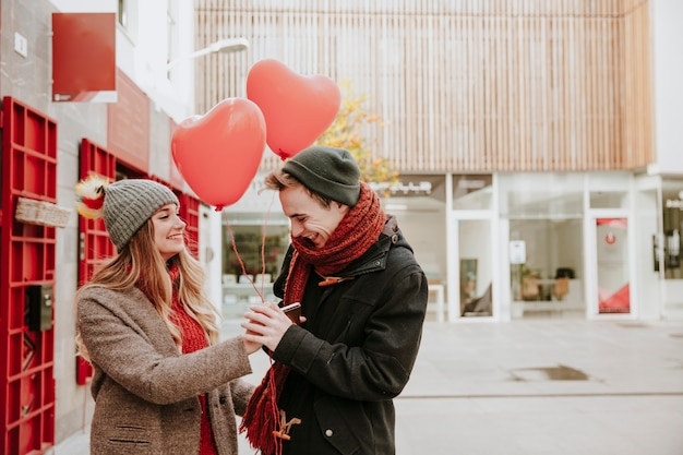 Woman giving heart balloons to smiling boyfriend
