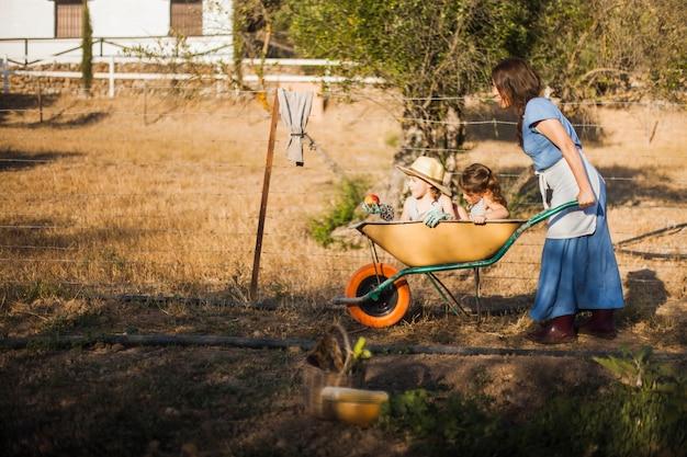 Woman giving her children ride in wheelbarrow
