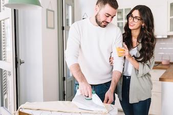 Woman giving juice to boyfriend ironing