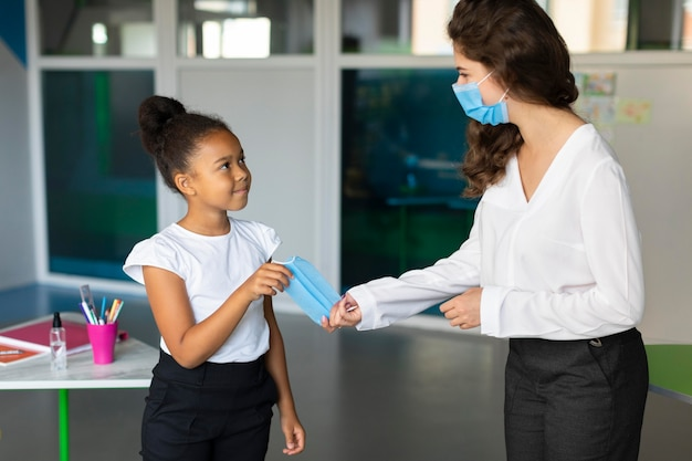Woman giving a medical mask to a student