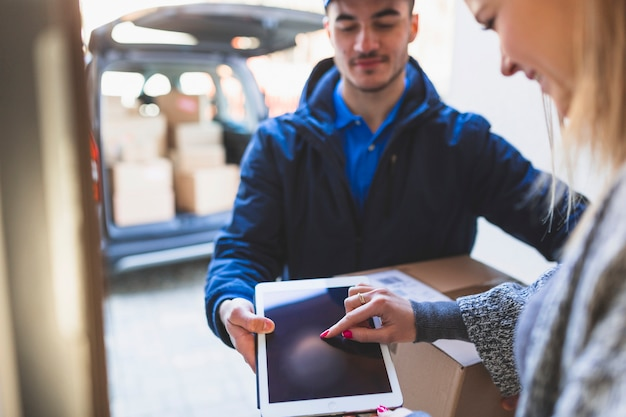 Woman giving online signature to deliveryman