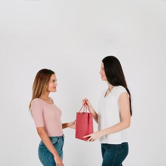 スタジオでガールフレンドに紙袋を与える女性