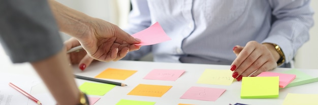 Woman giving pink sticker to colleague at table at workplace in office goals and objectives in