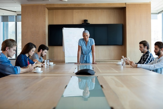 Женщина дает представление своим коллегам в конференц-зале в офисе