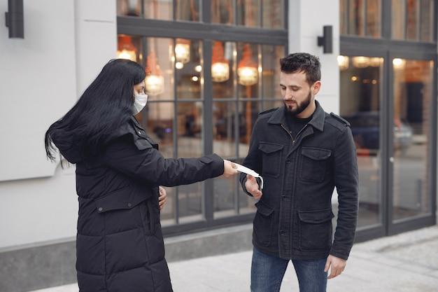 男に防護マスクを与える女性