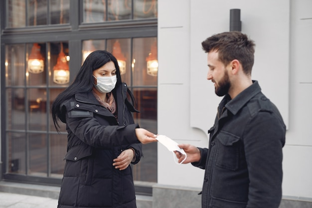 Женщина дает защитную маску мужчине