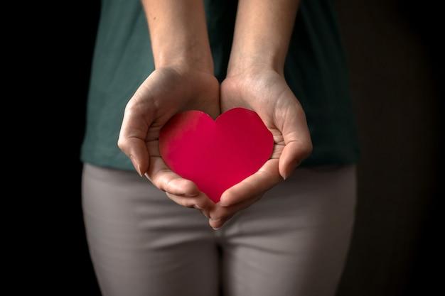 Женщина дает жест красное сердце. рука с красным сердцем. медицинское страхование, день донора органов и фото концепции благотворительности