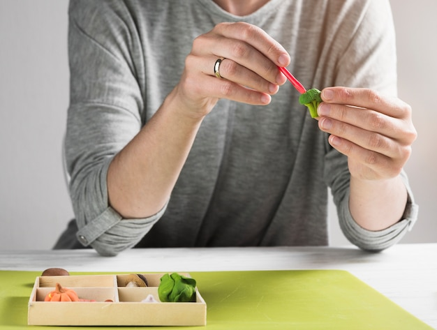 점토에서 브로콜리를 만드는 동안 점토의 모양을주는 여자