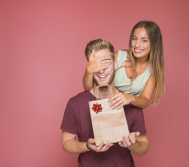 Woman giving shopping bag gift to her boyfriend by covering his eyes