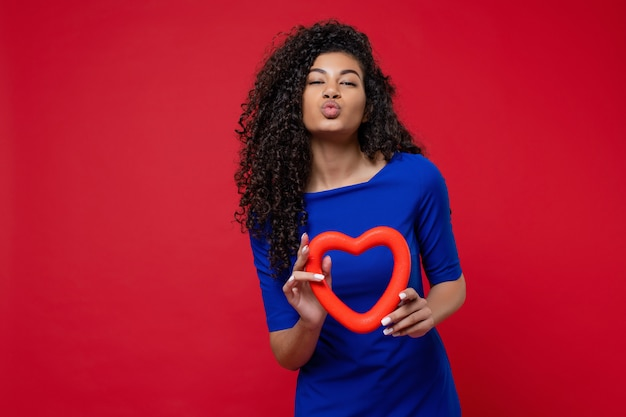 Woman giving smooch kiss with heart shape wearing dress on red wall