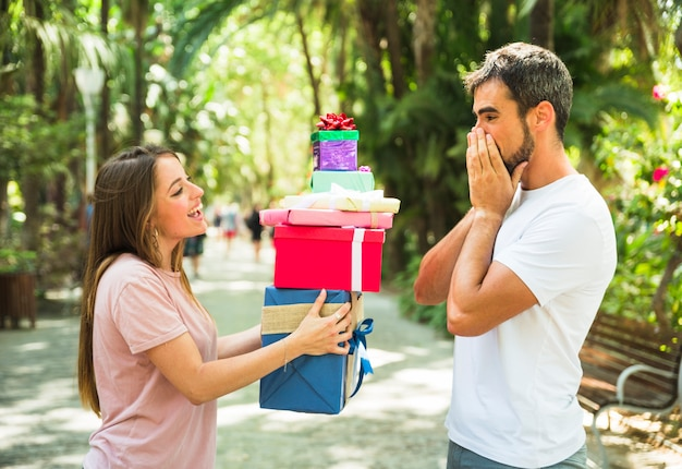 Woman giving stack of gifts to her surprised boyfriend