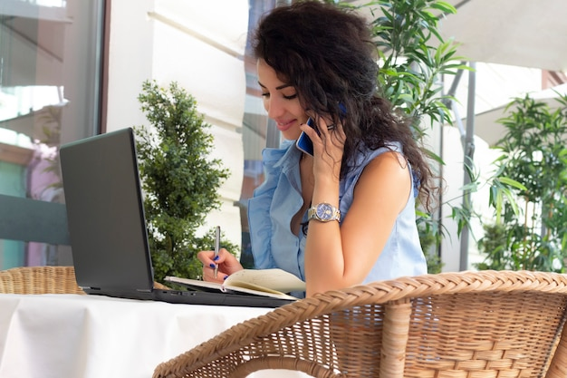 Woman in glass working remotely with laptop and phone in cafe. beautiful brunette using notebook in cafe. happy businesswoman calling on mobile phone and taking. freelance