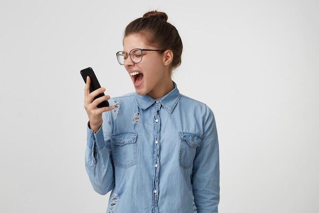 Una donna con gli occhiali, vestita con una camicia di jeans alla moda