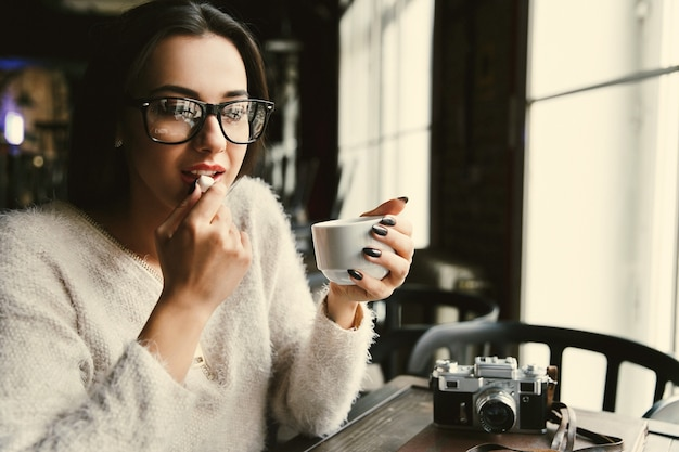 Woman in glasses drinks coffee and eats sugar at the table in bright cafe