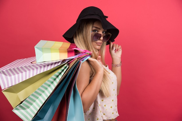 Woman in glasses and hat holding her shopping bags on red wall .