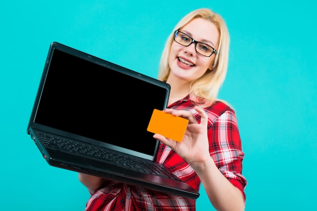 Woman in glasses hold laptop and businesscard