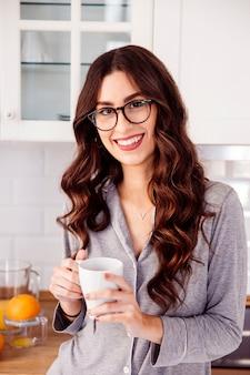 Woman in glasses holding mug