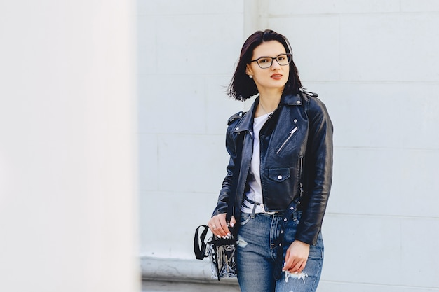 Woman in glasses in leather jacket on street